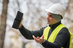 Hard times: engineer showing his empty wallet. Hard times: construction worker showing his empty wallet Stock Photo