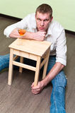 Hard times in life. Drunken man sitting on floor with glass of alcohol and holding stool Stock Image