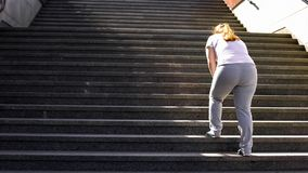 Hard to climb stairs for obese girl, victory over fatigue for goal achieving royalty free stock images