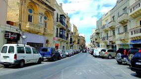 Hard traffic in Mosta, Malta. MOSTA, MALTA - JUNE 14, 2018: The busy traffic in Il-Kbira street, lined with old mansions, stores and cafes, on June 14 in Mosta stock footage