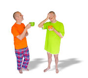 Hard Wake-up. A couple of twin man drinking coffee after waking up. One is in green nightdress, holding an orange cup, the other is in pajamas with an orange T Stock Images