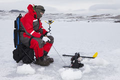 Hard Water Fishing. Man ice fishing on a cold winter day Stock Photos