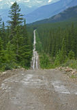 The Hard Way. A very long and narrow gravel road in the mountains Royalty Free Stock Photos