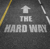 Hard way. Black asphalt road with the text 'the hard way' painted on the surface royalty free stock images