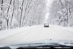 Hard winter traffic with car on snow coverd road Royalty Free Stock Images