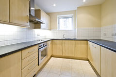 Hard wood finish modern kitchen. Contemporary kitchen in birch wood finisn and gray stone imitation worktop stock images
