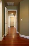 Hard Wood Hallway. Empty Hallway inside a modern home with hard wood flooring and open doors Stock Photos