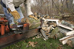 Hard at Work. Man running log splitter with large pile of split logs foreground and whole logs background Stock Photos