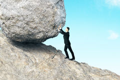 Hard work concept. Side view of young businessman pushing huge rock up mountain. Beautiful background. Hard work concept stock photos