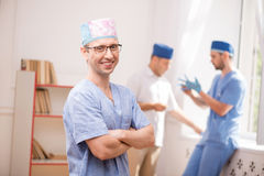 Hard work of doctors. Selective focus on the smiling surgeon wearing blue medical uniform and glasses standing aside with crossing arms looking at us. His Stock Photos