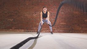 Female crossfit instructor proves that training ropes are a very dynamic workout. Slow motion stock video