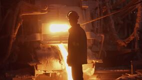 Hard work in a foundry. Metal smelting furnace in steel mill. Molten metal pouring, metallurgy, steel casting foundry