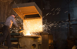Hard work in the foundry, worker controlling iron smelting in furnaces. Sparks. stock photo