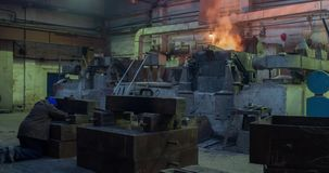 Hard work in the foundry, worker controlling iron smelting in furnaces, too hot and smoky working environment. Metal stock video footage