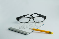 Hard work for an idea. Block notes with drawn lamp representing an idea after an hard work Royalty Free Stock Photo