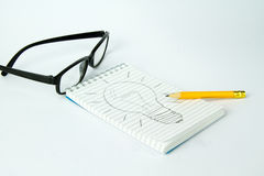 Hard work for an idea. Block notes with drawn lamp representing an idea after an hard work Royalty Free Stock Photos