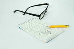 Hard work for an idea. Block notes with drawn lamp representing an idea after an hard work Stock Photos
