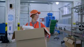 Hard work women in factory, smiling strong female into helmet and coveralls carries big heavy box with plastic bottles