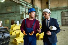 Discussing Workflow with Superior. Hard-working bearded technician wearing overall and hardhat sharing ides concerning workflow with mixed-race superior while stock photo