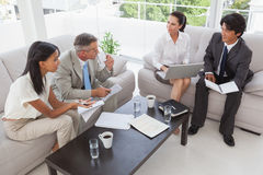 Hard working business people sitting down Stock Photos