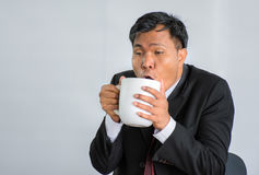 Hard working businessman Fatigue Drinking coffee /Isolate. Handsome bearded businessman drinking coffee isolated on grey Stock Images