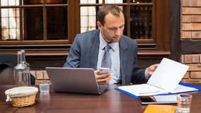 Hard working businessman in restaurant with laptop and mobile phone. Stock Image