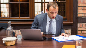 Hard working businessman in restaurant with laptop and pad. Stock Images