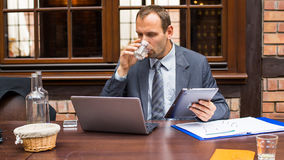 Hard working businessman in restaurant with laptop and pad. He is drinking water. Stock Photos