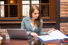 Hard working businesswoman in restaurant with laptop. Stock Images