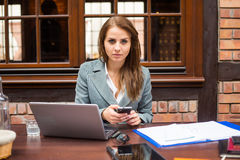 Hard working businesswoman in restaurant with laptop and mobile phone. Close-up Stock Photos