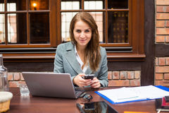 Hard working businesswoman in restaurant with laptop and mobile phone. Stock Images