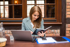 Hard working businesswoman in restaurant with laptop and notebook. Royalty Free Stock Image