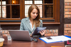 Hard working businesswoman in restaurant with laptop and pad. Stock Image