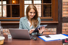 Hard working businesswoman in restaurant with laptop and pad. Stock Photography