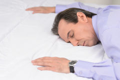 After the hard working day. Tired mature businessman sleeping on. The sofa Stock Image