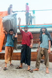Hard working dockers in traditional dhow wharfage port. DUBAI, UAE - 16 JUL 2014: Hard working dockers in traditional dhow wharfage port Royalty Free Stock Image