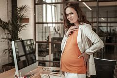 Hard-working expecting woman feeling uncomfortable and unpleasant. Pregnant state. Hard-working expecting woman feeling uncomfortable and unpleasant and staying stock photos