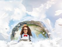 Creative inspiration of young female writer. Hard-working female writer using typing machine while sitting at the table with flying paper planes and Earth globe royalty free stock photo