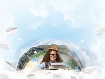 Creative inspiration of young female writer. Hard-working female writer using typing machine while sitting at the table with flying paper planes and Earth globe royalty free stock photography