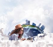 Creative inspiration of young female writer. Hard-working female writer using typing machine while sitting at the table with flying papers and Earth globe among stock photo