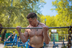 A hard-working guy is doing sports. Exercises in the park Stock Image