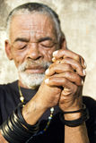 The hard working hands. Senior African man with folded hands - focus on the hands stock image