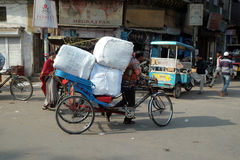 Hard working Indians pushing heavy load through streets of Delhi Stock Photography