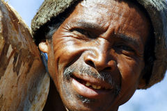 Hard working man carrying a tree trunk - MADAGASCAR Royalty Free Stock Photography
