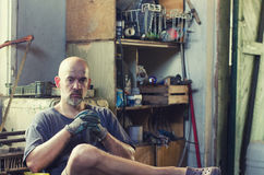 Hard working man sitting in his workshop Royalty Free Stock Image
