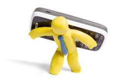 Hard working manager. Plasticine man carries mobile phone isolated on white stock image