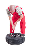 Hard-working mechanic changing car wheel tire Royalty Free Stock Images