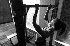 Hard working persistent woman keeping herself fit. Importance of sport. Hard working good looking persistent woman doing chin ups and focusing on this physical Stock Photos