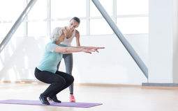 Hard working persistent woman squatting. Think about your health. Serious good looking persistent women standing on a mat and squatting while working out with a Royalty Free Stock Photography