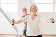 Hard working pleasant woman exercising with a resistance band Royalty Free Stock Images